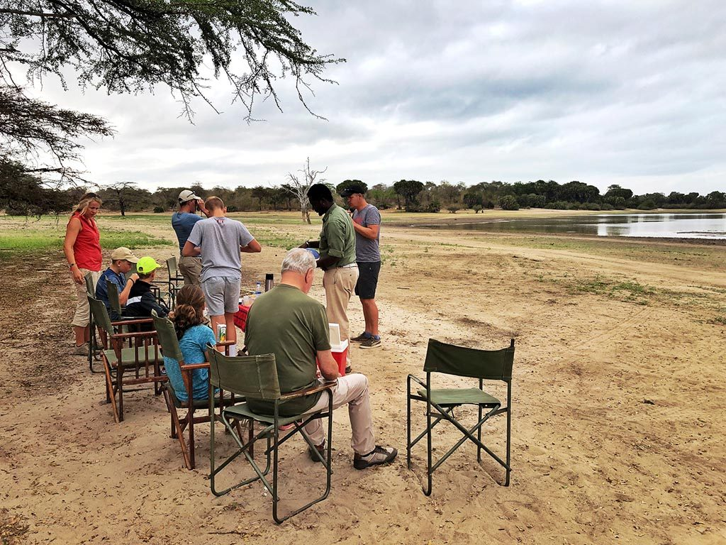A family with children is having breakfast in front of the land rover and near the lake during a morning safari in the Selous Game Reserve.