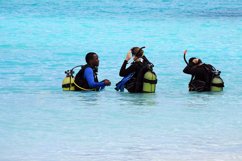 A professional diver teaches two women how to dive in the crystal waters of Nungwi.
