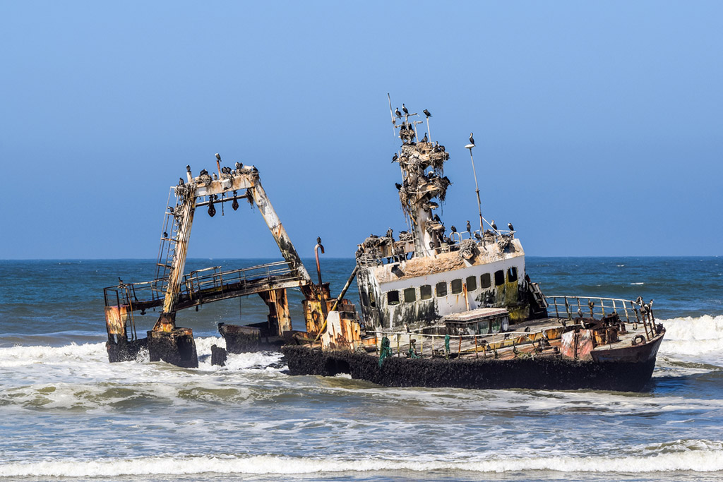 Old shipwreck Zeila at the Atlantic Coast between Swakopmund and Henties Bay along the famous Skeleton Coast in Namibia, Africa. Cormorants on the wreck.