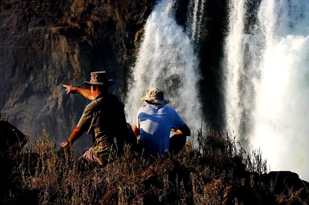 Two men look over the edge of Victoria falls gorge.