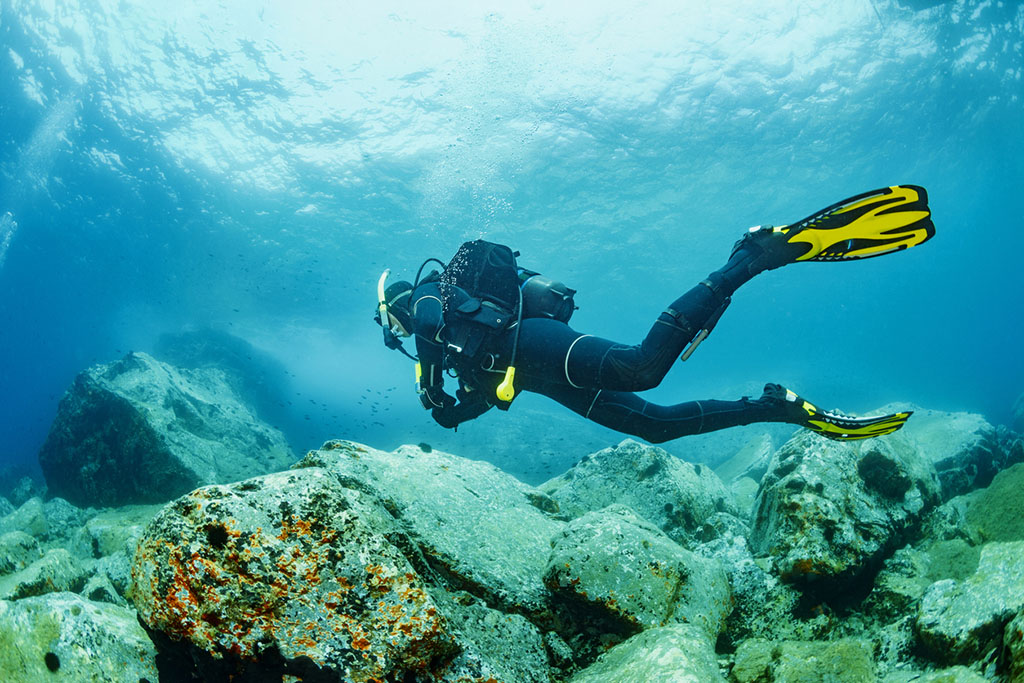 Scuba diving. Beautiful sea. Underwater scene with male scuba diver, enjoy in blue, shallow water. Scuba diver point of view.