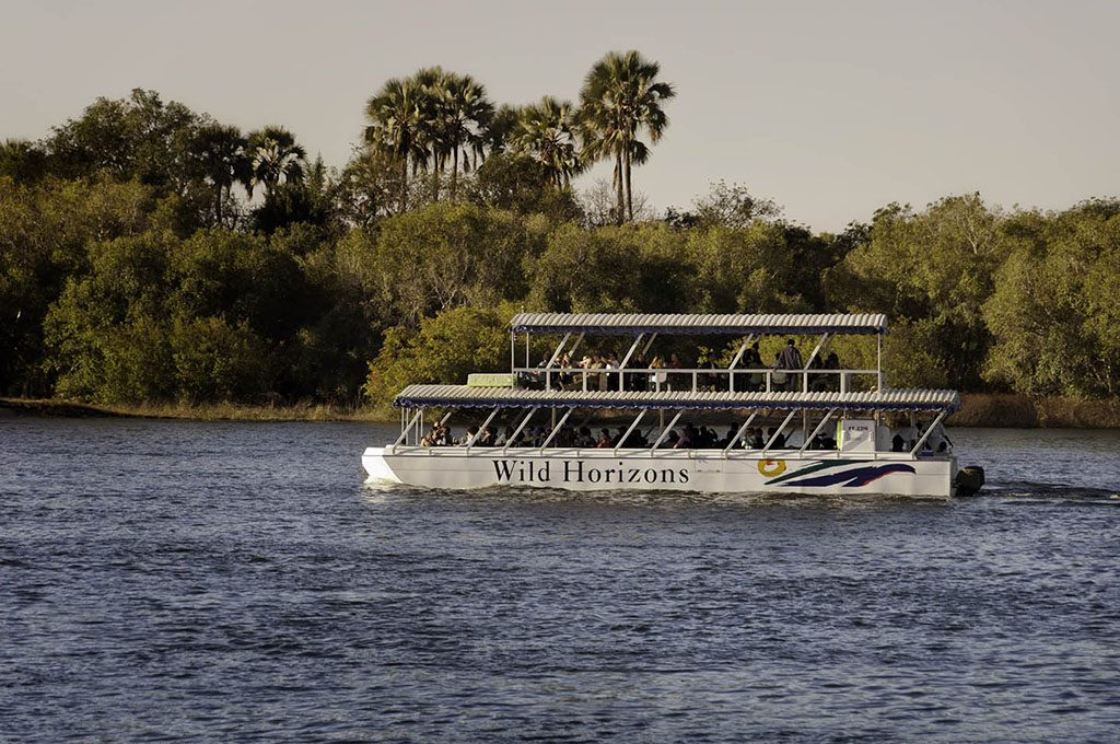 Tourists enjoying a sunset cruise on the the placid upper Zambezi River on a double decker cruise boat copy