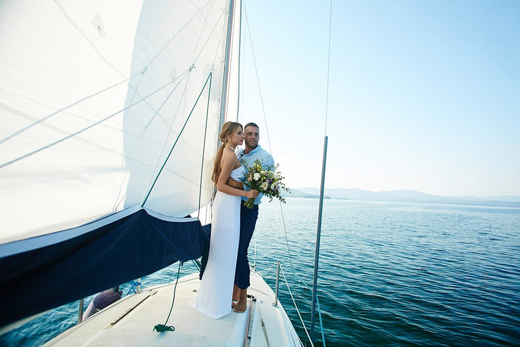Happy married couple traveling by yacht during honeymoon