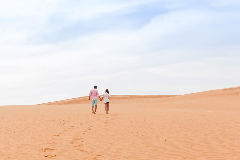Young Man Woman Walking In Desert Couple Girl And Man Hold Hands Back Rear View Sand Dune Landscape Nature Background