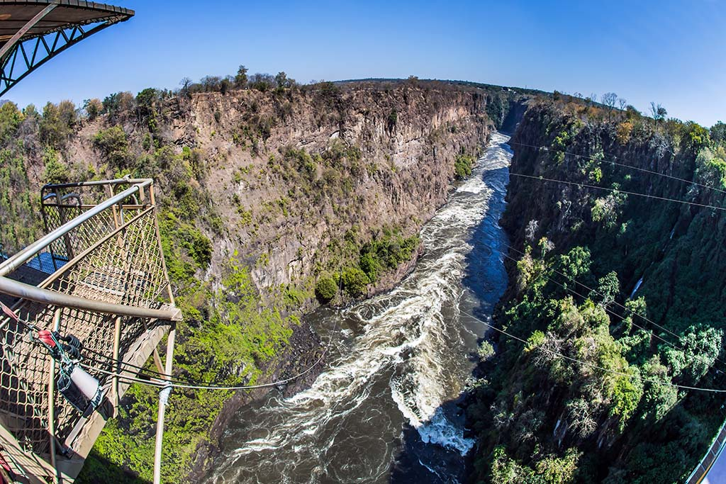 Ropes for canopy and bungee jumping area stretched over raging Zambezi River. The waterfall Victoria Falls on the Zambezi River