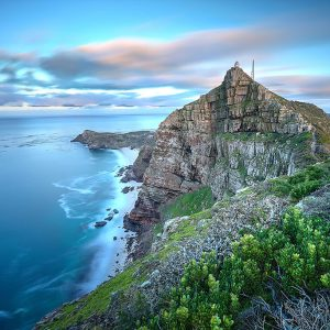 Cape Point, South Africa as time stands still - slight movement in the water and clouds as the sun rises in the back. There's a lighthouse on top of the cliff which serves to warn passing ships that there's land.