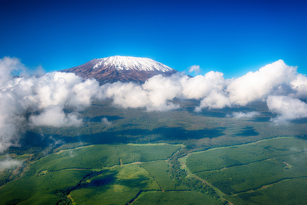 Aerial image of Mount Kilimanjaro, Africa's highest mountain, with snow and white puffy clouds
