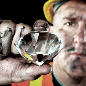 A dirty diamond miner covered in soot shows off a precious gem
